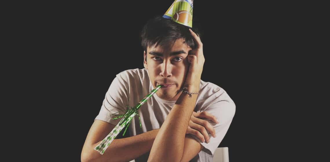 Junger Mann mit Partyhut und Partytröte