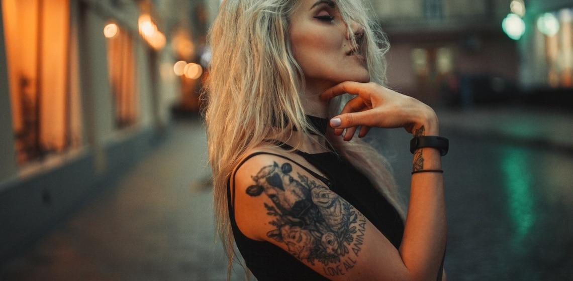 Blondine mit Tattoos am Arm