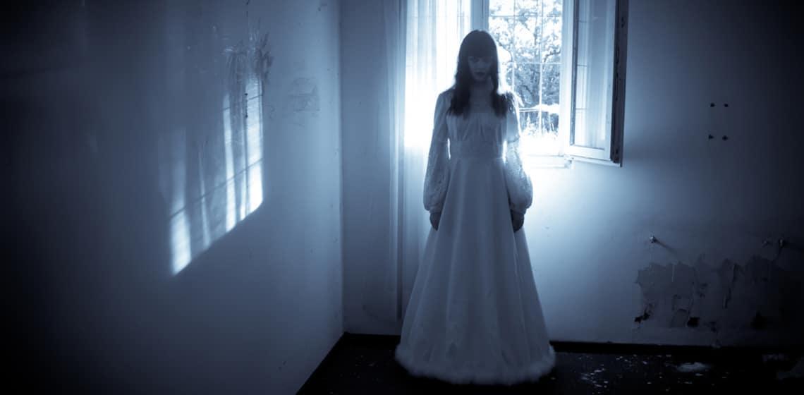 Frau in weißem Kleid vor Fenster bei Nacht