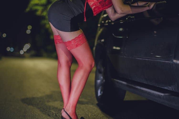 Prostituierte mit roten Strapsen bei Auto