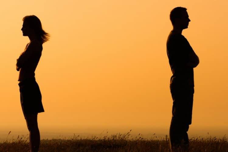 Paar mit Rücken zueinander stehend bei Sonnenuntergang