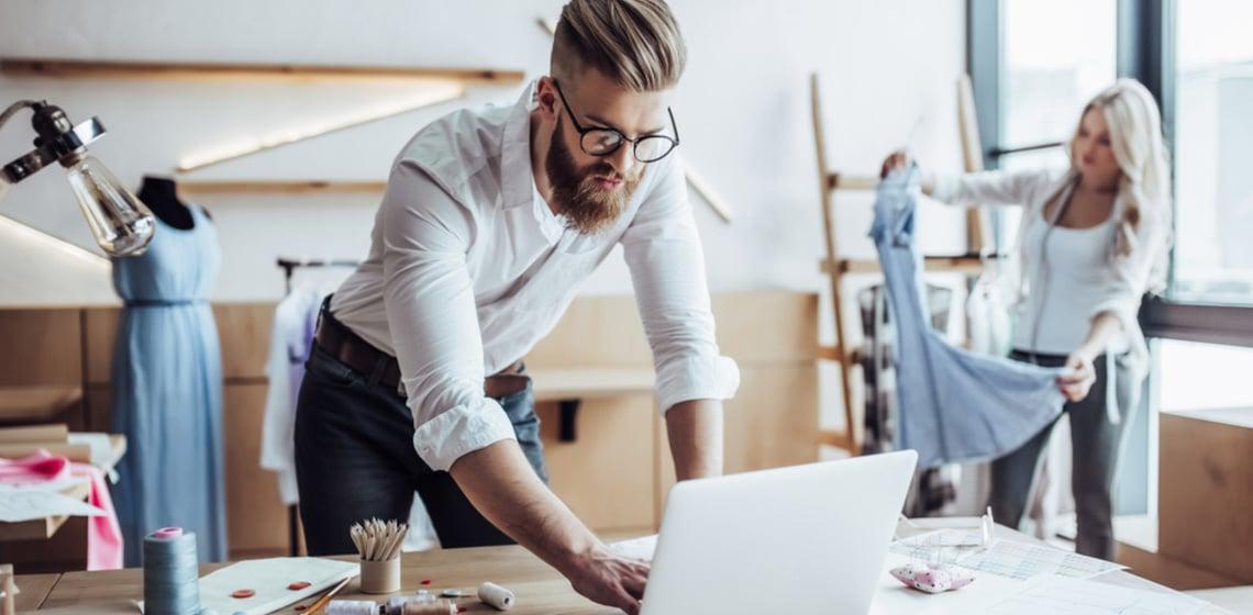 Stylisher Mann mit Brille schaut auf Laptop